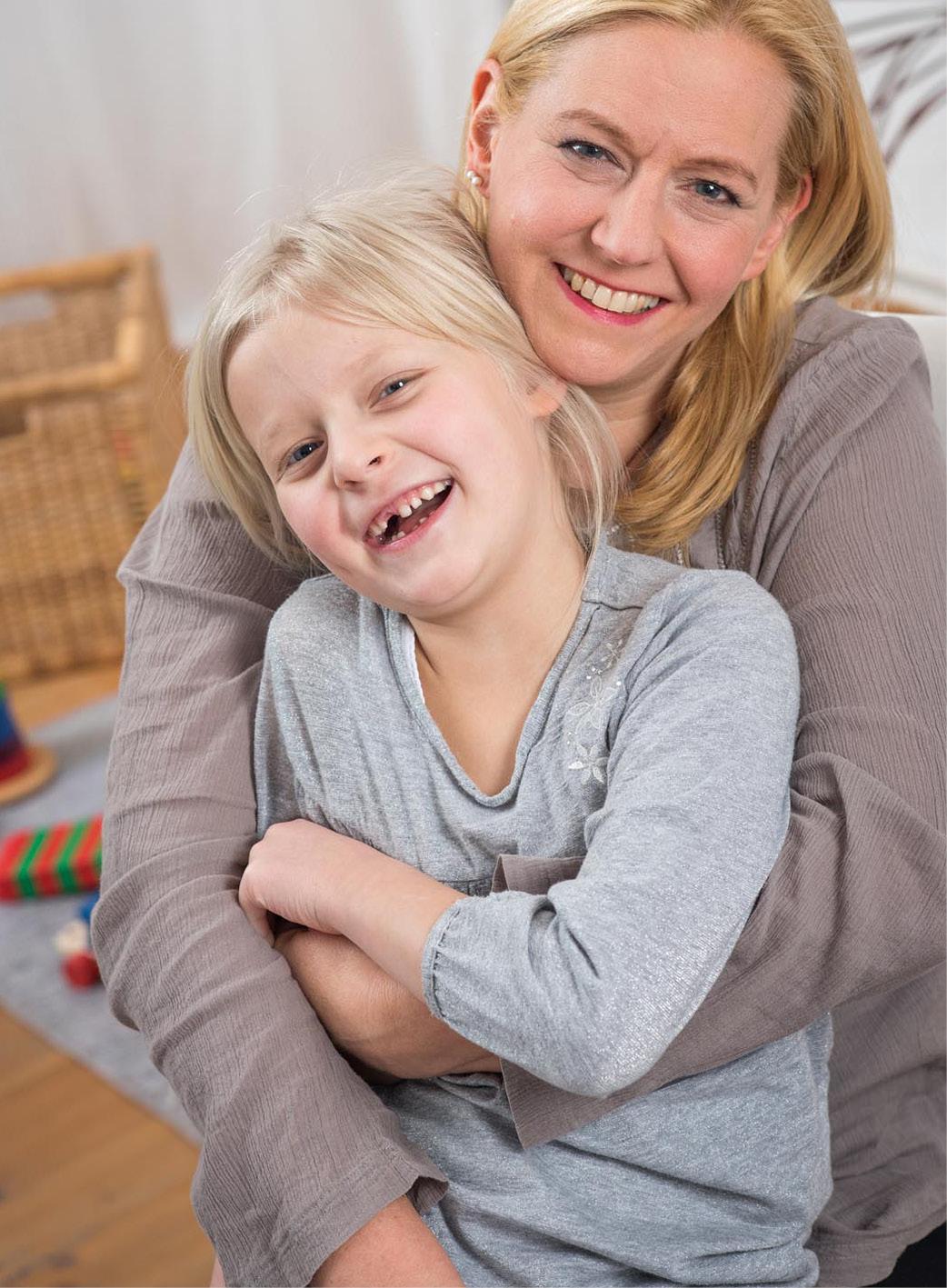 Lachende Mutter mit Tochter im Arm